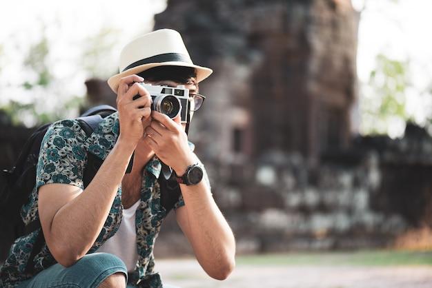 Jeune homme photographe voyageur avec sac à dos prenant une photo avec son appareil photo