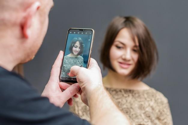 Jeune homme photographiant une fille
