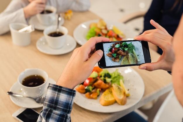 Jeune homme photographiant son assiette de nourriture