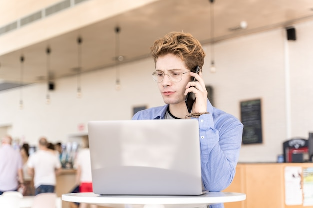 Jeune homme avec des piercings parlant sur un téléphone mobile avec une expression inquiète assis à une table avec un ordinateur portable travaillant sur un coworking
