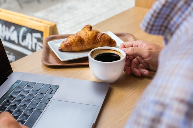 Jeune homme, pigiste assis dans un café, buvant du café et travaillant sur un ordinateur portable. composition de style de vie avec lumière naturelle