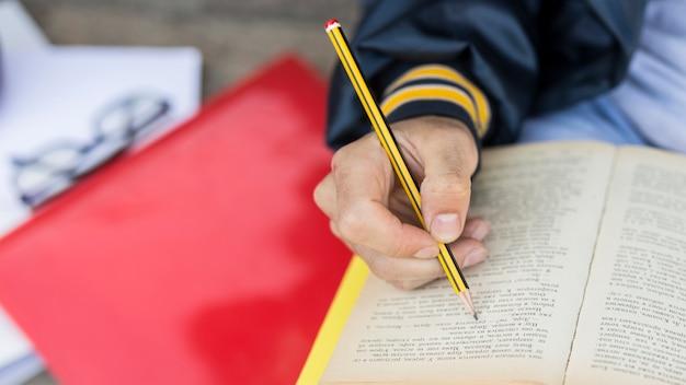 Jeune homme piquant dans un livre