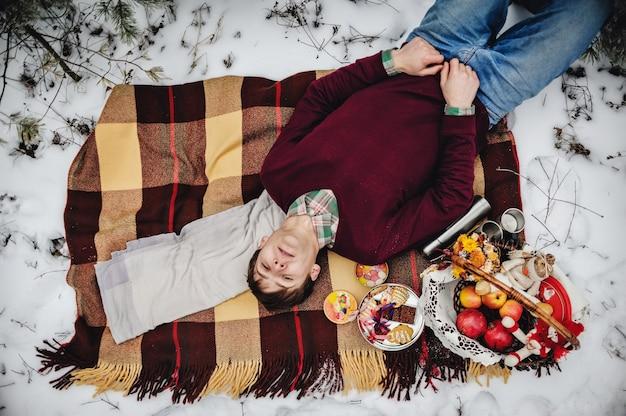 Jeune homme sur un pique-nique en hiver