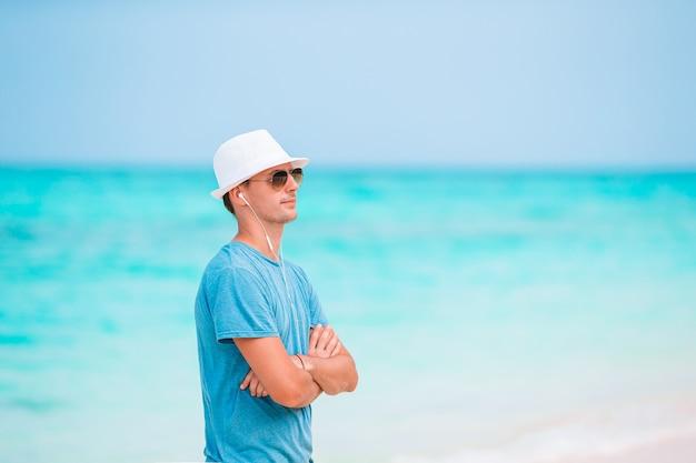 Jeune homme sur la plage blanche en vacances