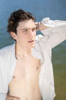 Jeune homme sur la plage avec chemise blanche et déboutonnée et cheveux mouillés