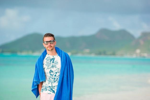 Jeune homme sur une plage de sable blanc en vacances