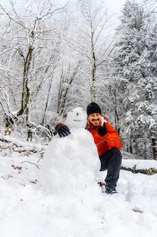 Un jeune homme plaisantant avec un bonhomme de neige dans la forêt enneigée du parc naturel d'artikutza à oiartzun près de san sebastian, gipuzkoa, pais vasco. espagne