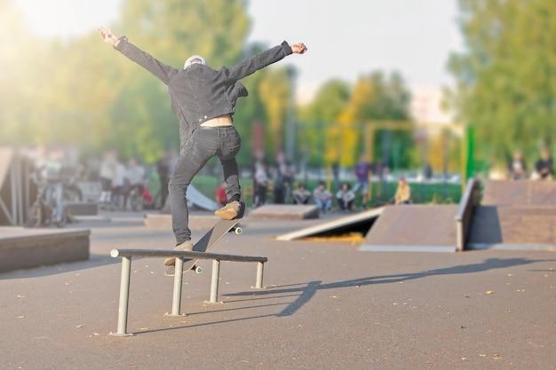 Jeune homme sur une planche à roulettes en vol, adolescent apprenant à faire de la planche à roulettes dans le parc
