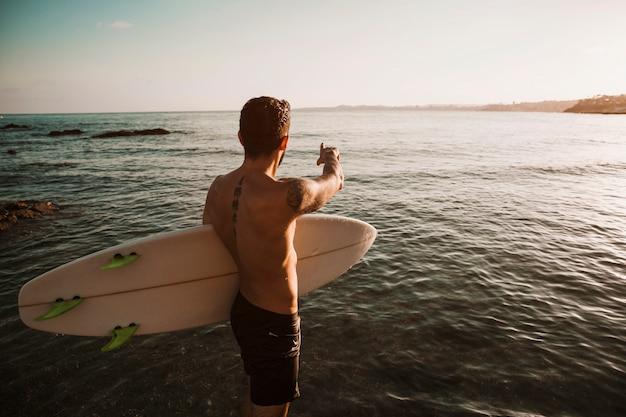 Jeune homme, planche surf, quelque part, doigt
