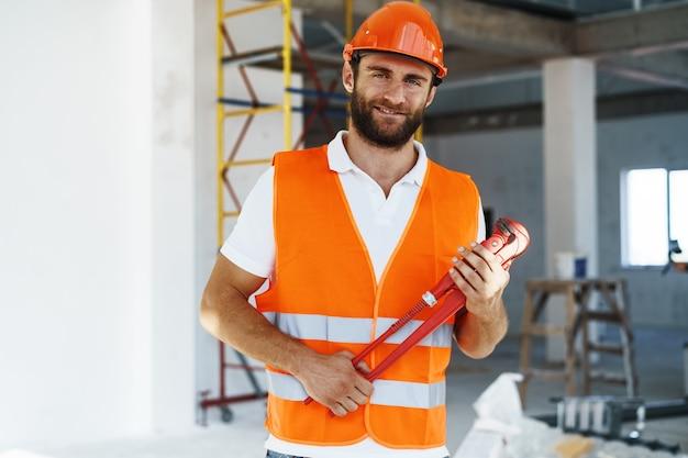Jeune homme plombier tenant une clé à pipe sur un chantier de construction à l'intérieur