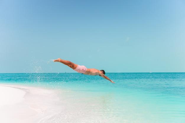 Jeune homme plongeant dans la mer turquoise