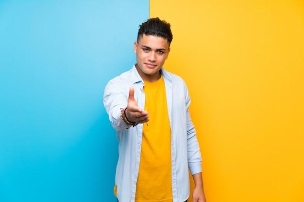 Jeune homme sur la poignée de main isolée fond coloré après bonne affaire