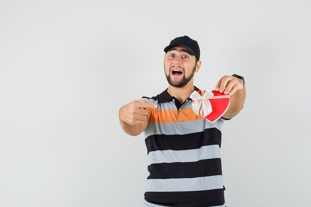 Jeune homme pointant sur la boîte actuelle en t-shirt, casquette et à la jolly. vue de face.