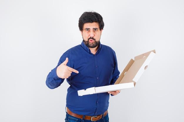 Jeune homme pointant une boîte à pizza en chemise, jeans et ayant l'air confiant. vue de face.