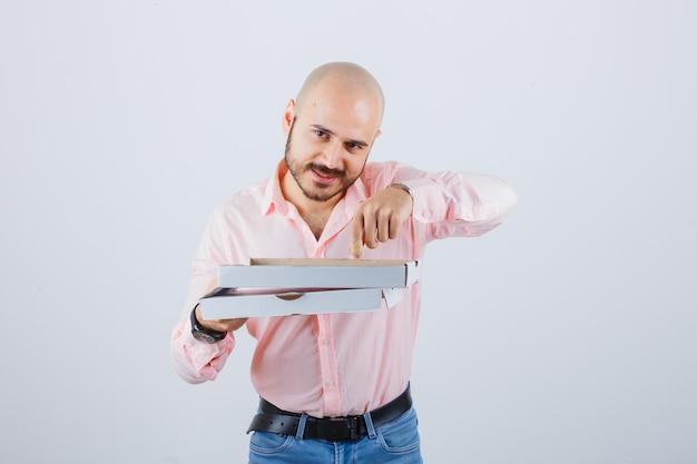 Jeune homme pointant une boîte à pizza ouverte en chemise, jeans et l'air heureux. vue de face.
