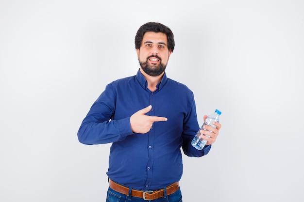 Jeune homme pointant une bouteille d'eau en chemise bleue et jeans et à l'optimisme. vue de face.