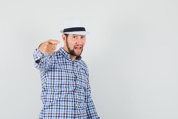 Jeune homme pointant la caméra en chemise à carreaux, chapeau et à la confiance. vue de face.