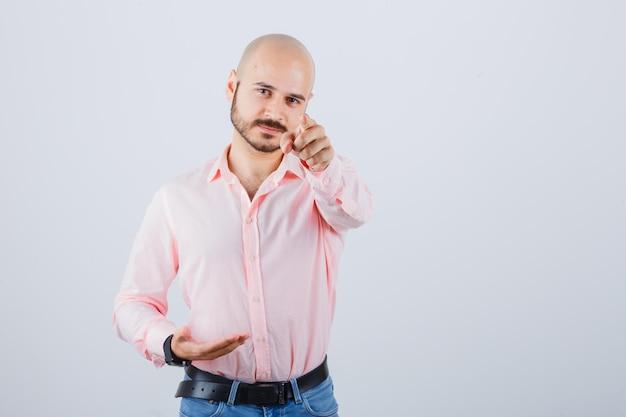 Jeune homme pointant sur la caméra en chemise rose, vue de face de jeans.