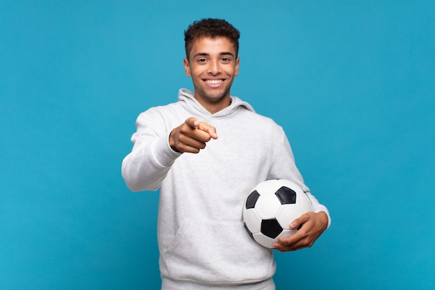 Jeune homme pointant la caméra avec un sourire satisfait, confiant et amical, vous choisissant. concept de football