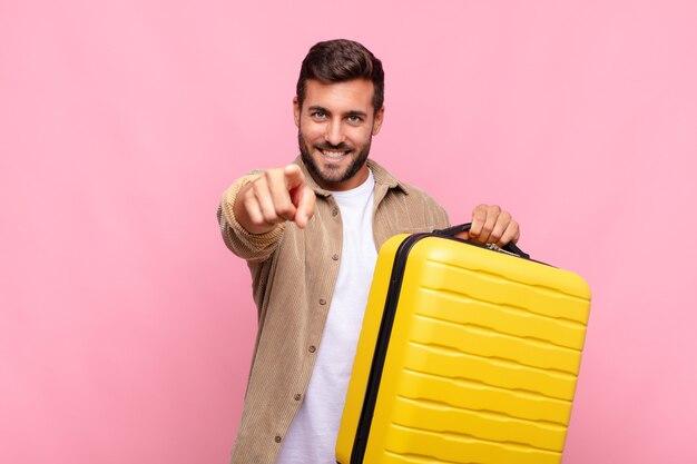 Jeune homme pointant la caméra avec un sourire satisfait, confiant et amical, vous choisissant. concept de vacances