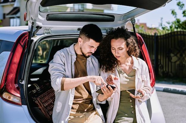 Jeune homme pointant sur la carte dans le smartphone tout en expliquant à sa femme où ils vont se déplacer et en lui montrant l'endroit où s'arrêter pour se reposer