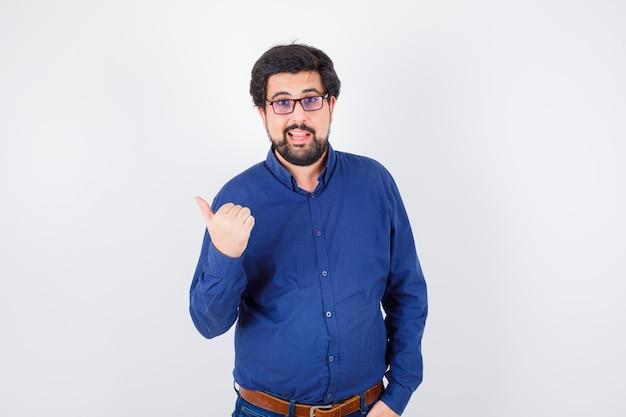 Jeune homme pointant de côté en chemise bleu royal, lunettes, vue de face.