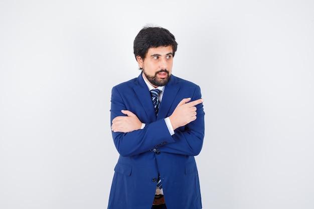 Jeune homme pointant de côté en chemise, veste, cravate et regardant concentré, vue de face.