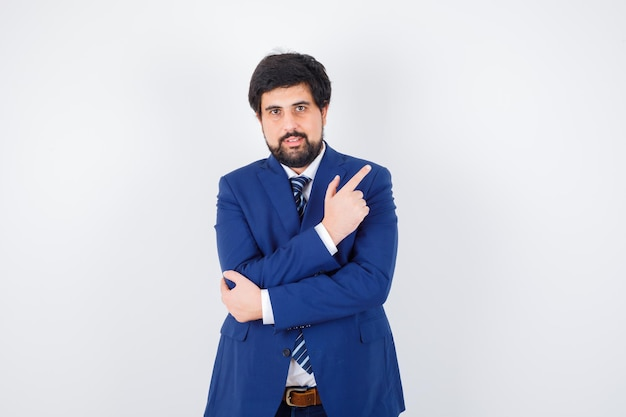 Jeune homme pointant de côté en chemise, veste, cravate, vue de face.