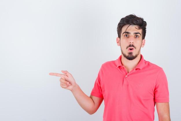 Jeune homme pointant de côté en t-shirt rose et l'air surpris, vue de face.