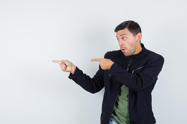 Jeune homme pointant sur le côté en t-shirt, veste et semblant sûr. vue de face.