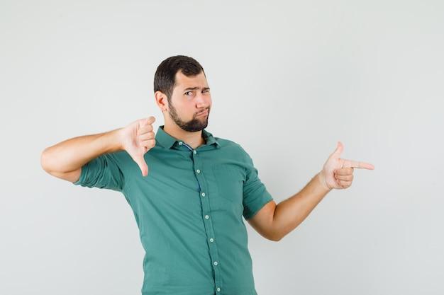 Jeune homme pointant de côté tout en montrant le pouce vers le bas en chemise verte et l'air insatisfait. vue de face.