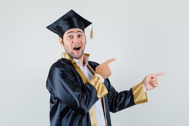 Jeune homme pointant de côté en uniforme d'études supérieures et à la joyeuse vue de face.