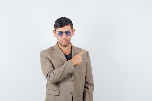 Jeune homme pointant sur le côté en veste marron grisâtre, lunettes bleues et semblant sérieux. vue de face. espace pour le texte