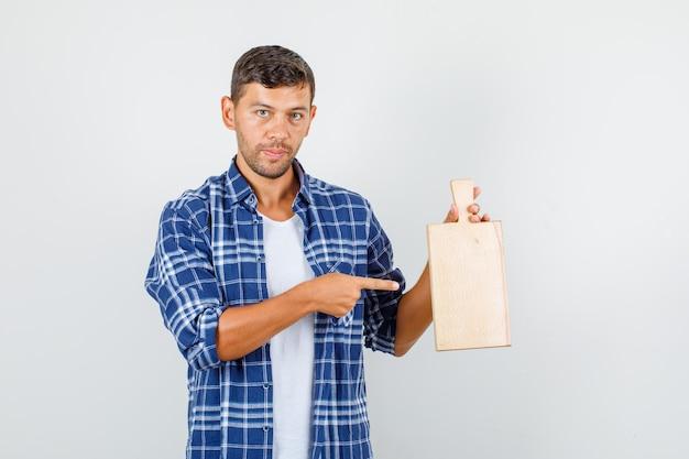 Jeune homme pointant le doigt sur une planche à découper en chemise et à la recherche de sérieux. vue de face.