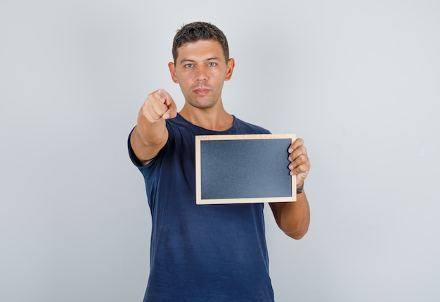 Jeune homme pointant le doigt vers la caméra avec tableau noir en t-shirt bleu foncé, vue de face.