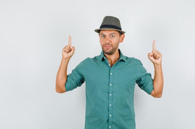 Jeune homme pointant les doigts en chemise, chapeau et à la confiance