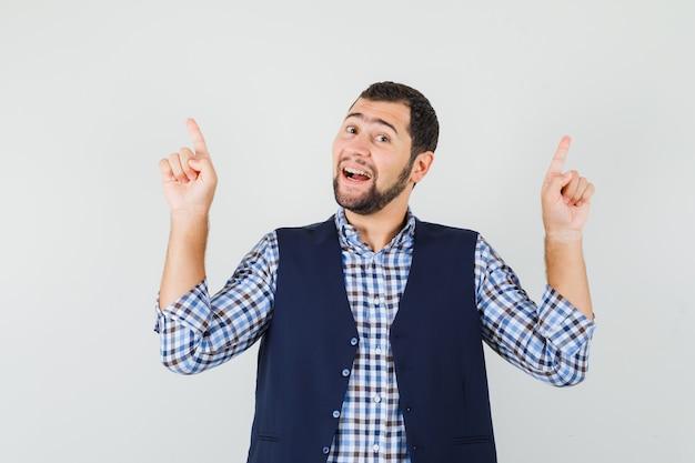 Jeune homme pointant les doigts vers le haut en chemise, gilet et espoir, vue de face.