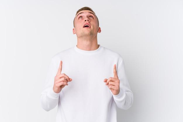 Jeune homme pointant à l'envers avec la bouche ouverte