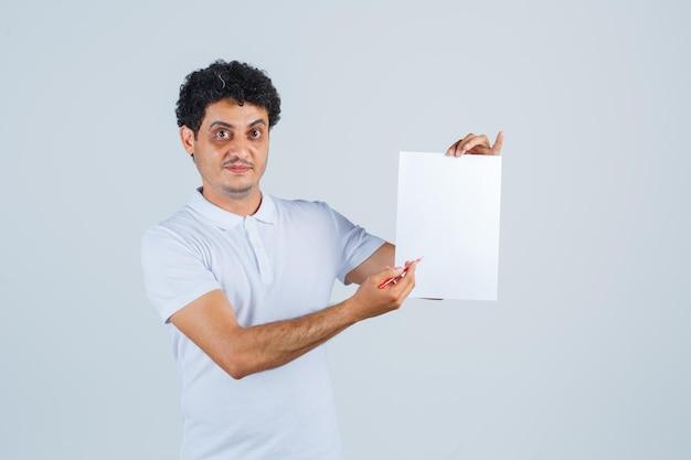 Jeune homme pointant sur une feuille de papier avec un stylo en t-shirt blanc et ayant l'air confiant. vue de face.