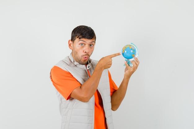 Jeune homme pointant sur le globe de l'école en t-shirt, veste et à la surprise. vue de face.