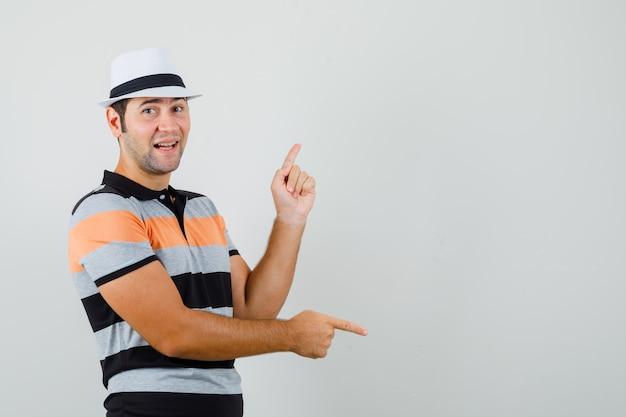 Jeune homme pointant de haut en bas en t-shirt rayé, chapeau et à la recherche amusée. vue de face. espace pour le texte