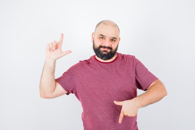 Jeune homme pointant de haut en bas en t-shirt rose et hésitant. vue de face.