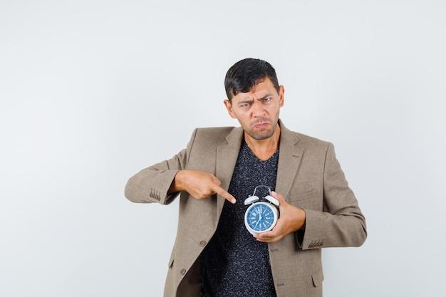 Jeune homme pointant l'horloge en veste marron grisâtre et l'air mécontent, vue de face.