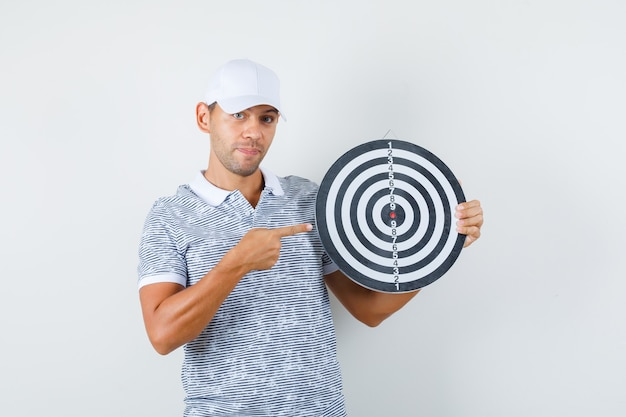 Jeune homme pointant sur le jeu de fléchettes en t-shirt et casquette et à la bonne humeur