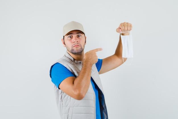 Jeune homme pointant sur un masque médical en t-shirt, veste, casquette et à la perplexité. vue de face.