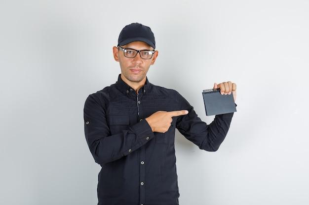 Jeune homme pointant mini cahier en chemise noire avec capuchon