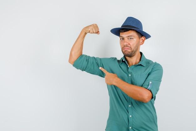 Jeune homme pointant sur le muscle en chemise, chapeau et à la confiance.