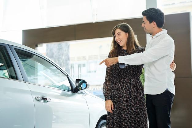 Jeune homme pointant sur la nouvelle voiture et la montrant à sa femme, alors qu'ils se tenaient dans la salle d'exposition de voiture