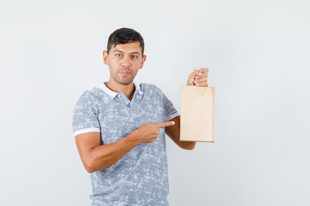 Jeune homme pointant sur une planche à découper en t-shirt et à la recherche positive