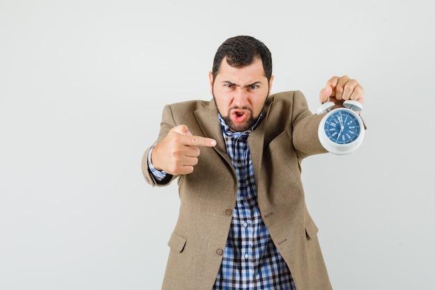 Jeune homme pointant sur réveil en chemise, veste et à la nervosité. vue de face.